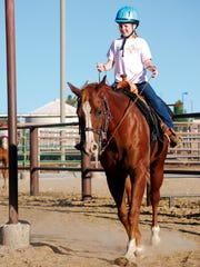 A young rider in the NMSU Therapeutic Riding program appears on horseback.