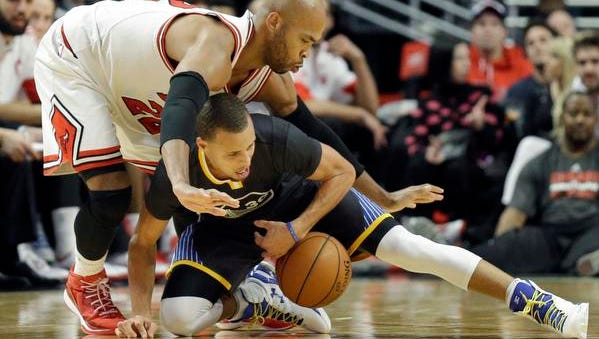 Golden State Warriors guard Stephen Curry (30) controls the ball against Chicago Bulls forward Taj Gibson (22) during the second half of an NBA basketball game in Chicago on Saturday, Dec. 6, 2014. The Warriors won 112-102