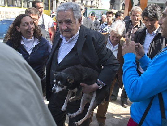 Uruguayan President Jose Mujica carries his dog, Manuela,