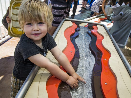 Cade Lanteigne, 2, Mesa, gets to put his hands in the water as part of the grand opening of the new Colorado River Adventure exhibit at the Arizona Sea Life Aquarium, Friday, May 19, 2017.