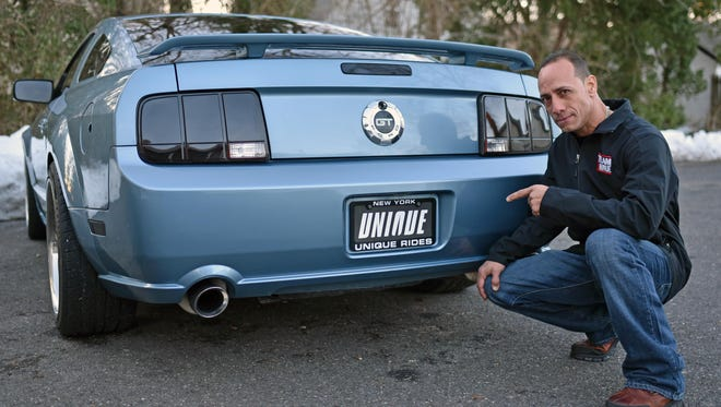 """Santos """"Saint"""" Pagan points to a custom """"Unique Rides"""" license plate on the back of his Ford Mustang."""