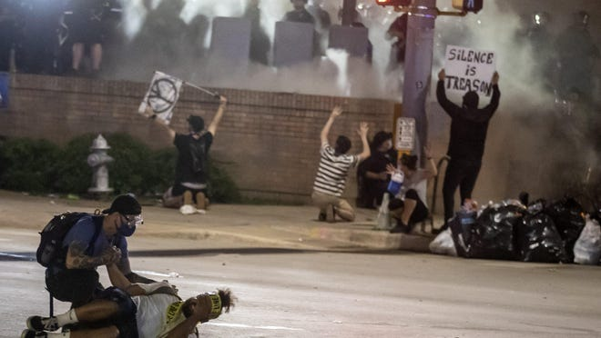People help a protester after he was shot with a rubber bullet under Interstate 35 freeway in Austin Texas.  Demonstrators protest over the police killing of George Floyd  Saturday, May 30, 2020.
