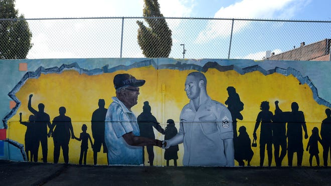 A mural that honors Luther Manus Jr., 92, a retired Erie teacher and counselor, is shown Friday at Manus Sunoco at 26 E. 12th St. The mural, created by artists Ceasar Westbrook and Antonio Howard, was sponsored by Erie Arts & Culture.