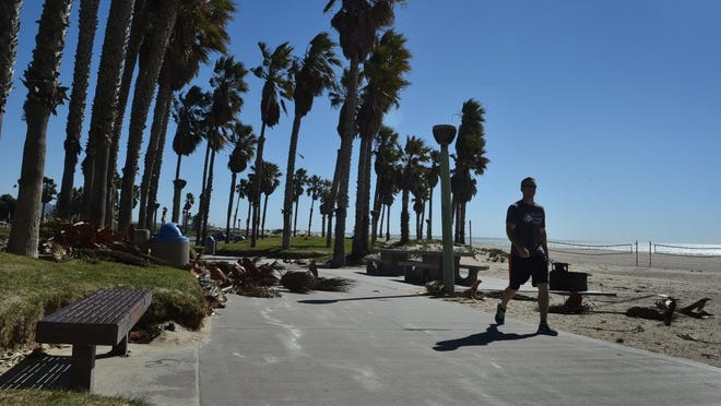 "ANTHONY PLASCENCIA/THE STAR Chris Nerlich, of Port Hueneme, takes a walk along the beach Monday as strong winds leave palm fronds littered across the sidewalks. ""I'm enjoying the warm weather,"" said Nerlich. ""Not so much the wind, but the warm weather."""