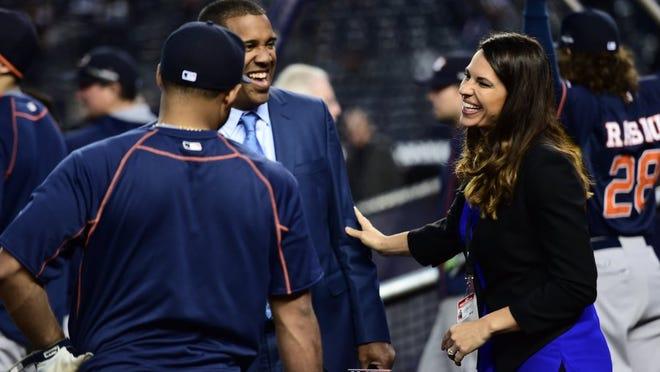 ESPN analysts Jessica Mendoza and Eduardo Perez talk before a playoff game at Yankee Stadium.