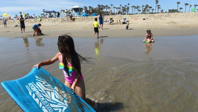 KAREN QUINCY LOBERG/THE STAR Victoria Luna (left), 8, of Oxnard, experiences afternoon winds at Hueneme Beach cooling the temperatures down to the low 70s while much of Ventura County felt much greater heat on Sunday.