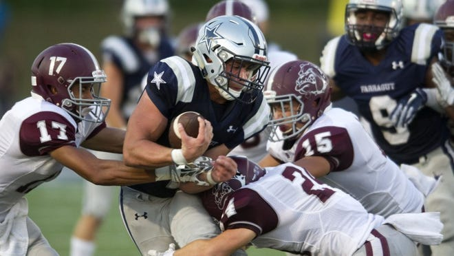 Farragut's Cooper Hardin (1) gets tackled by Bearden's Tyson Bivins (17), Sam Coffin (24) and Alex Majors (15) during a game last season.