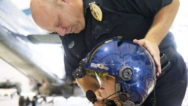 Lee Tramel, Knox County Sheriff's Office's chief of administration, fits a flight helmet onto Joshua Collins while Joshua was touring KCSO's aviation facilities at Downtown Island Home Airport. According to his mother, Jessica Collins, the boy's interest in Batman came after he saw some television shows about the superhero and then meeting a K-9 officer from KPD.