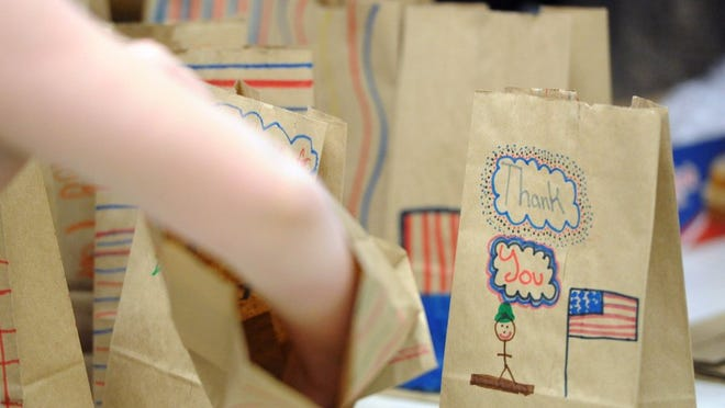 Students decorate and fill lunch bags with snacks at Corryton Elementary School on Wednesday. The bags will be distributed to veterans during the upcoming 20th Honor Air Knoxville flight, which flies World War II, Korean War and Vietnam War veterans free of charge to Washington to visit historic memorials. (ADAM LAU/NEWS SENTINEL)