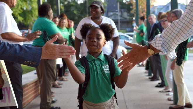 photos by AMY SMOTHERMAN BURGESS/NEWS SENTINEL Six year-old Le'Brya Williams is greeted by board members and staff on the first day of school at Emerald Academy on Wednesday, July 27, 2016. The charter school, which opened in 2015, will enroll 250 students in its second year.