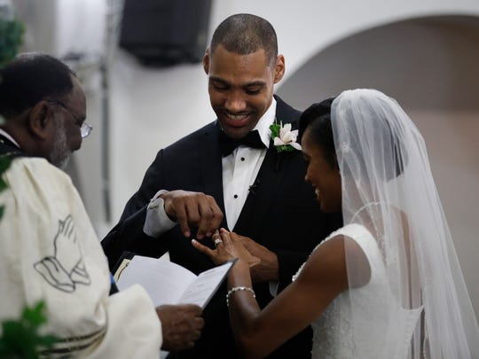 Jamie Nieto smiles as he puts a ring on the finger of his bride Shevon Stoddart during a wedding ceremony Saturday.