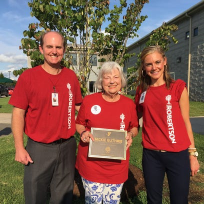 """Chad Smith, executive director of the Robertson County Family YMCA and district development director Diana Pelham honor longtime donor Jackie Guthrie with a plaque. On the YMCAs 20th birthday celebration, held Thursday, July 28, the three pose in front of the tree planted in her honor. It reads, """"Jackie Guthrie - For her lifelong dedication to the Robertson County Family YMCA. May her roots run deep here always."""""""