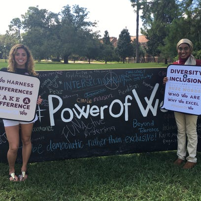 Vice Chair Gabbie Stratiotis and Chair Inam Sakinah pose in front of the Power of We banner on Landis Green.