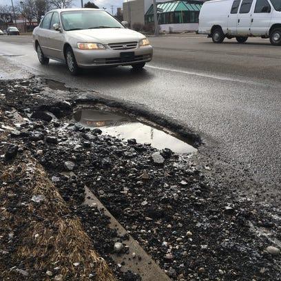 Crews work through rain to patch Lansing-area potholes