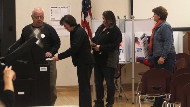 From left, election inspector Jack Hilburger of Irondequoit watches as Barb Egan casts her ballot at Laurelton Fire Department's meeting hall on Nov. 4, 2013.  Also waiting to cast ballots are Yvette Indovina and Sue Swift.