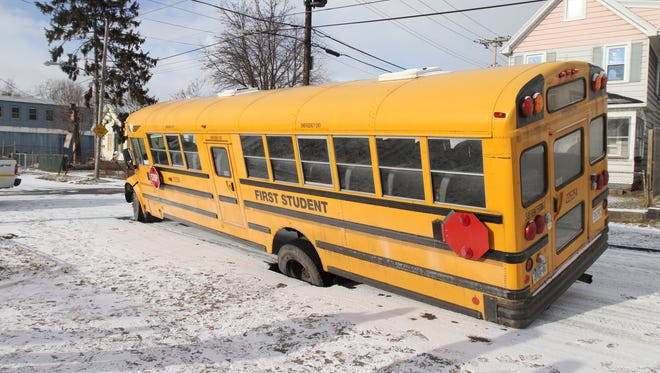A school bus fell into a hole on Colvin Street Monday.