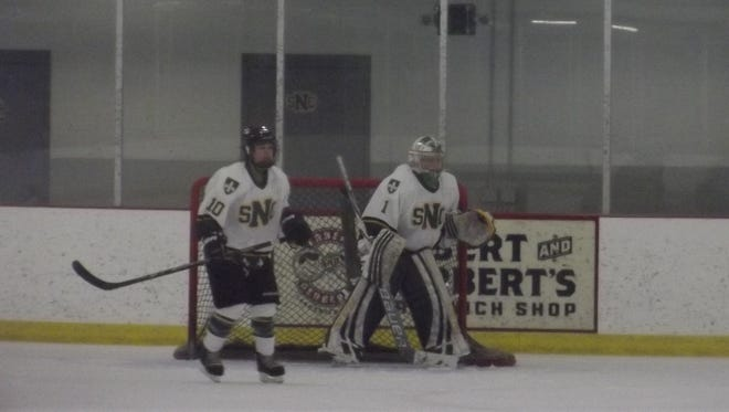 St. Norbert College freshman goalie Brianna Kelly and freshman defenseman Natasha Smith during a penalty kill in the third period of the Green Knights' 5-2 victory against the University of Wisconsin-Stevens Point at the Cornerstone Community Center on Jan. 3, 2015.