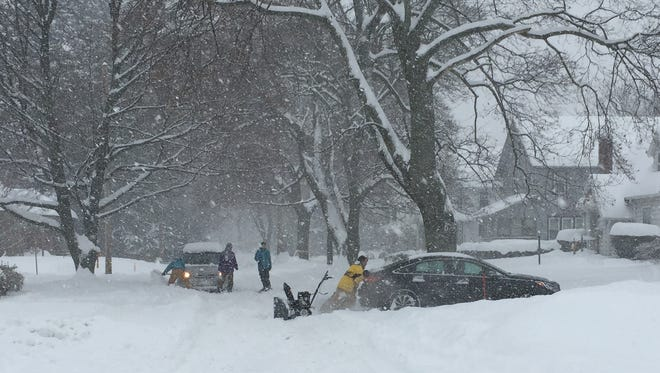 Several drivers try to free their  disabled cars on a side street in Irondequoit.