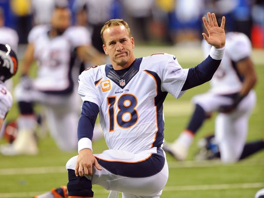 Denver Bronco quarterback Peyton Manning acknowledges his fans as he warms up before the start of an Oct. 20, 2013, game at his old Colts home, Lucas Oil Stadium.