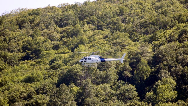 A law enforcement helicopter flies over a heavily wooded area as the search continues for two escaped prisoners from Clinton Correctional Facility, on Wednesday, June 24, 2015, in Owls Head, N.Y.