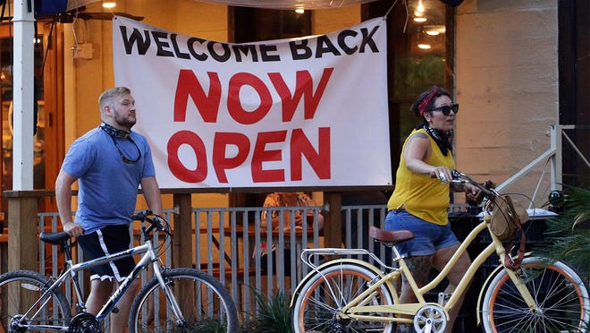 Two people walk their bicycles past a restaurant that reopened in San Antonio, Texas, earlier this month.