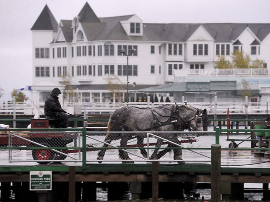 """""""Dray"""" horses haul cargo and supplies off incoming ferry boats Tuesday on Mackinac Island."""