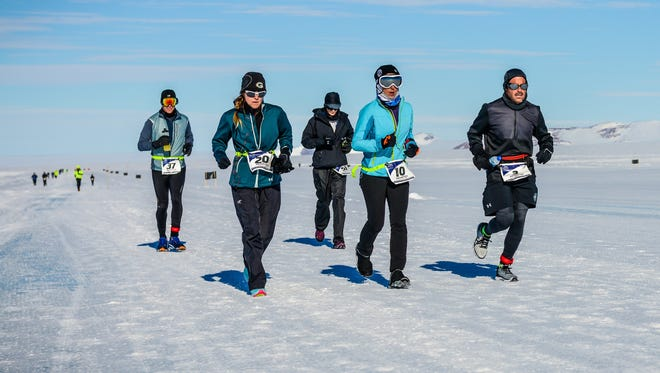 Deb Carneol (light blue jacket) and some fellow runners keep pace on the flat, barren, frozen, pure-white terrain at Novo Base, Antarctica, at the start of the 2018 World Marathon Challenge.