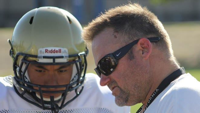 Desert Hot Springs football coach Will Littell explains a drill to one of his players during practice Wednesday, August 12.