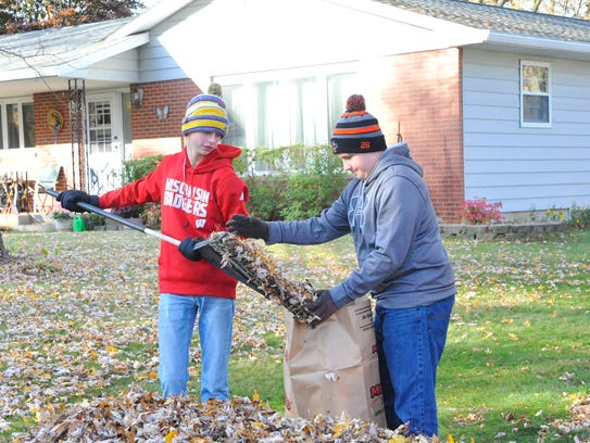 Cole Hanson pours a rake full of leaves into a bag