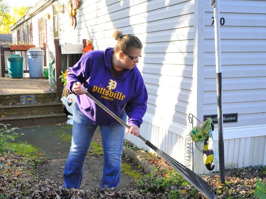 Barb Larson rakes leaves at a home on Katschef Street,