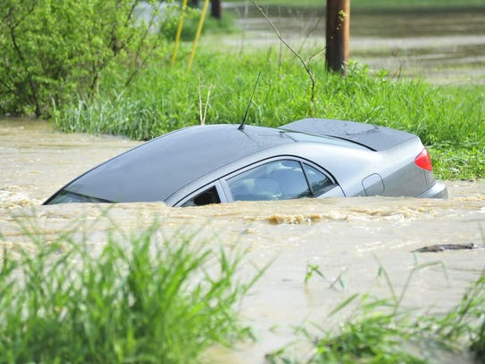 The driver of a car submerged in a river that crosses