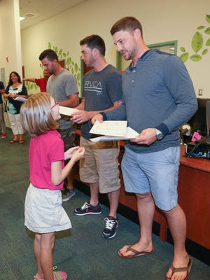 A student from Treeline Elementary School gives a card to Boston Red Sox catcher Ryan Lavarnway, right, Red Sox catcher Blake Swihart, center, and shortstop Deven Marrerro, second from left, after the players filled backpacks with non-perishable food items on behalf of Community Cooperative Ministries Incorporated.