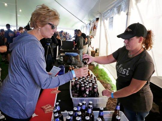 Ann Schneider of Fon du Lac gets a sample of Potosi beer Saturday September 24, 2016 at the Blue Harbor Craft Beer Festival in Sheboygan.