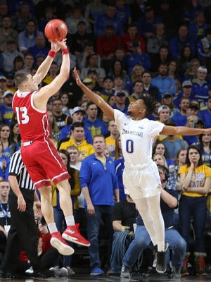 Matt Mooney #13 of South Dakota shoots over the arm of Brandon Key #0 of South Dakota State at the 2018 Summit League Basketball tournament at the Denny Sanford Premier Center in Sioux Falls.