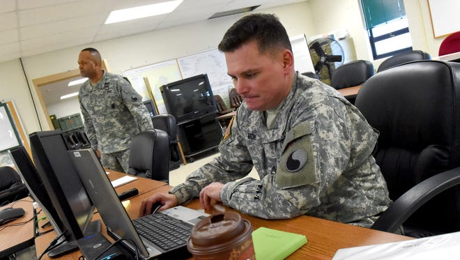 Sgt. 1st Class Robert Bond monitors communication and weather reports as he and Master Sgt. Gerald Johnson help man the command and control center for the winter storm at Thomas D. Howie Memorial National Guard Armory in Staunton on Thursday, March 5, 2015.