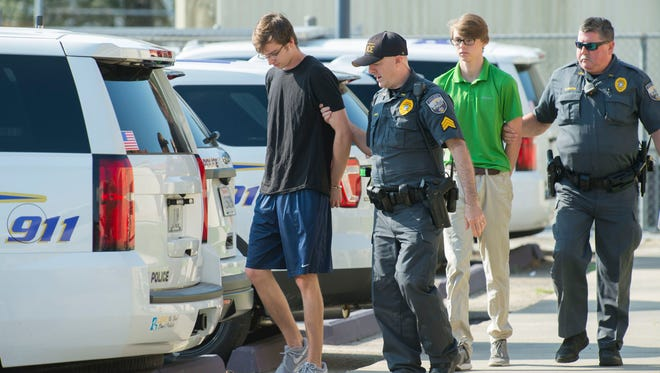 Zachary Hall, left and Sean Pennison, second from right, are escorted by LSU Police officers after being booked at the LSU Police Dept. headquarters on charges of hazing on Wednesday. Ten members of the Phi Delta Theta fraternity were arrested Wednesday on hazing charges in the death of Maxwell Gruver, a Louisiana State University fraternity pledge whose blood-alcohol content level was more than six times the legal limit for driving, officials said.  Matthew Alexander Naquin also faces a negligent homicide charge.