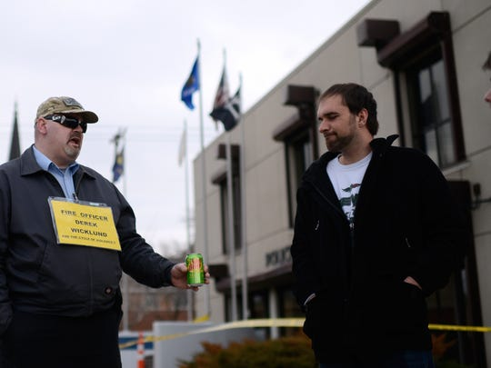 Bronson Smith, center, and Brandon Falish, both of Green Bay, discuss police behavior May 2 while standing in front of the Green Bay police station on Adams Street.