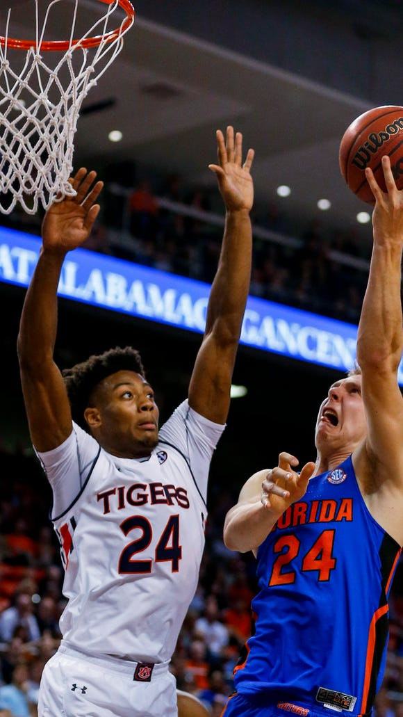 Florida guard Canyon Barry (24) shoots next to Auburn forward Anfernee McLemore (24) during the first half of an NCAA college basketball game, Tuesday, Feb. 14, 2017, in Auburn, Ala.