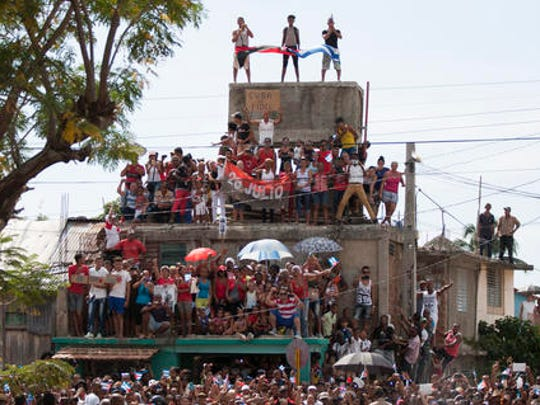People stand on a building to get a better view of the funeral procession carrying the ashes of Fidel Castro, the last stage of the convoy arriving to Santiago, Cuba, Saturday, Dec. 3, 2016. After a four-day journey across Cuba, Castro's ashes arrived to their final resting place in the eastern city of Santiago.
