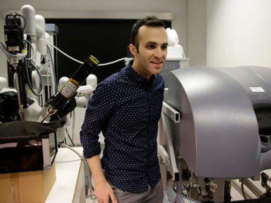 Iranian-born bioengineer researcher Nima Enayati stands as he works on a robotic surgery machine during an interview with the Associated Press at the Polytechnic University of Milan, Italy, Tuesday, Jan. 31, 2017. An Iranian researcher at Milan's Polytechnic University, Enayati was refused check-in Monday at Milan's Malpensa Airport for his U.S.-bound flight on Turkish Airlines after the Trump administration's executive order came down.
