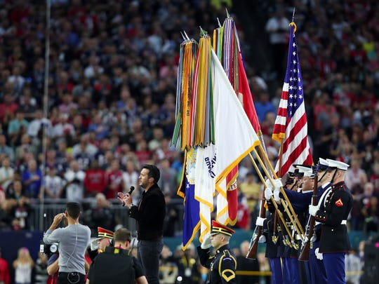 RIT graduate Kriston Lee Pumphrey (gray shirt) signs as country music singer and songwriter Luke Bryan performs the national anthem prior to Super Bowl 51 between the New England Patriots and the Atlanta Falcons at NRG Stadium on Feb. 5, 2017 in Houston.