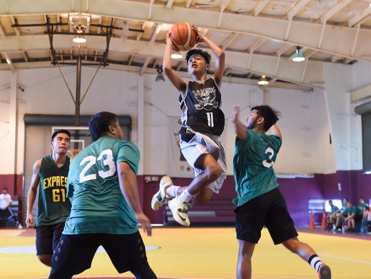 In this Jan. 22, 2017, file photo, Raiders player Ken Brozo (11) shoots over Bank of Guam Ifit defenders during the Bud Light Golden Hoops Classic Spring 2017 Tournament at Tamuning Gym.