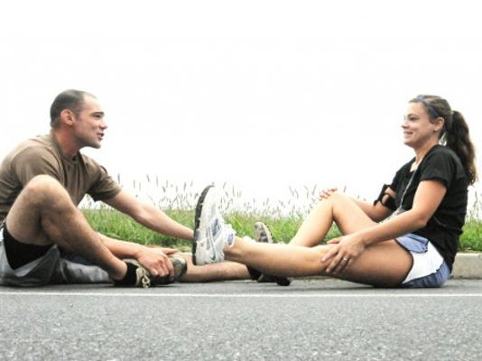 James Cummings and Amanda Lagana, both of Palmyra, stretch before a 5K on Labor Day 2012.  (LEBANON DAILY NEWS -- EARL BRIGHTBILL)