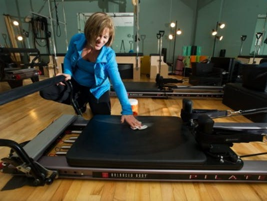 Denise Hart uses bleach wipes to clean off a reformer at her Pilates studio at Strictly Fitness in Springettsbury Township. Learn gym etiquette and talk with a fitness professional to build confidence while working out. (Photo by Paul Kuehnel)