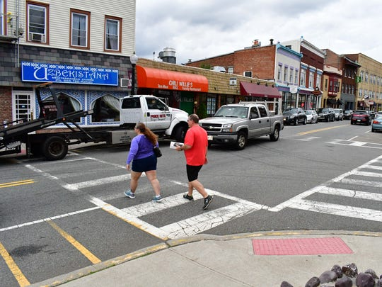 Pedestrians crossing the street at Main and Church streets on Monday. Undercover police officers were on hand to enforce pedestrian safety.