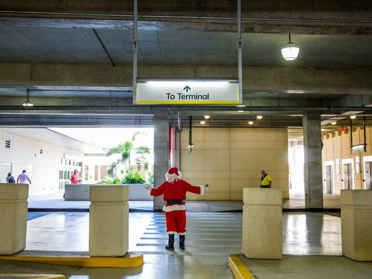 Jim Kirby of Estero greets Hertz customers while dressed as Santa at Southwest Florida International Airport on Friday, Dec. 22, 2017.