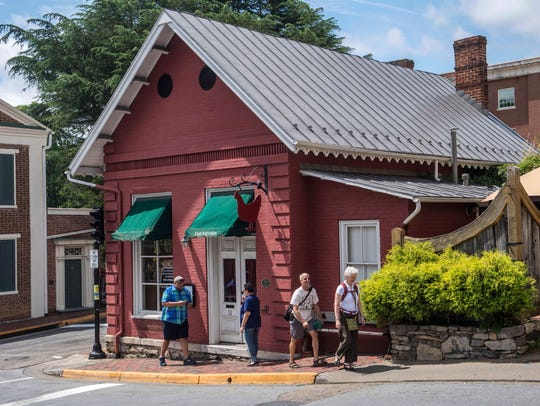 People walk past The Red Hen restaurant in Lexington, Virginia, Wednesday, June 27, 2018. Stephanie Wilkinson, the co-owner of the Virginia restaurant that refused to serve White House press secretary Sarah Huckabee Sanders, has resigned from a local business group. Wilkinson has ties to Pittsford.