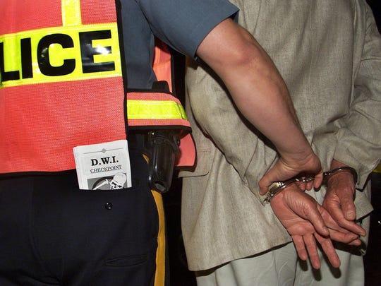 A suspected drunken driver is taken into custody at