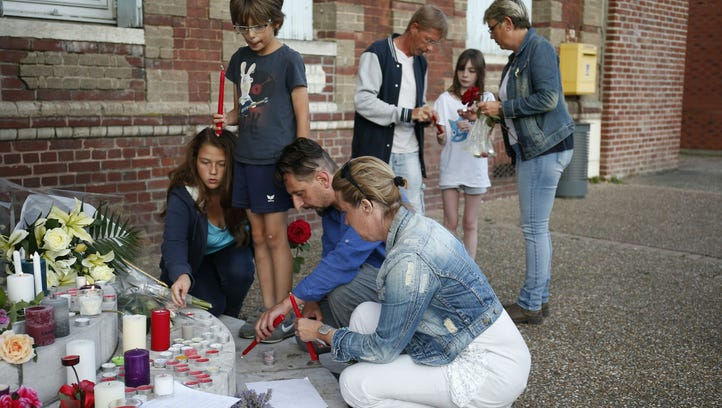 People light candles at city hall in Saint-Etienne-du-Rouvray,