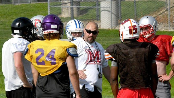 Lexington coach Taylor Gerhardt huddles with some of his South players in preparation for Saturday  night's NCOFCA All-Star Football Classic at Arlin Field.